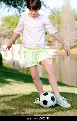 Dix ans, fille, jouant avec un ballon de soccer dans le parc Banque D'Images