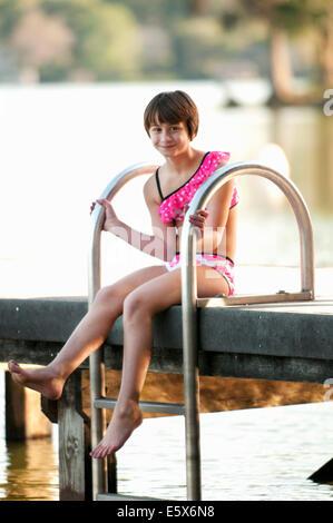 Portrait de dix ans, fille en bikini sitting on lake pier Banque D'Images