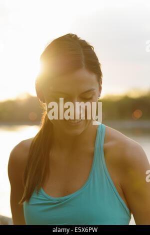 Portrait of young female runner sur le bord de mer au lever du soleil Banque D'Images