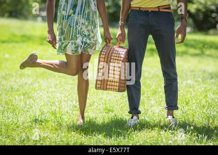 Portrait de jeune couple avec panier à pique-nique dans le parc