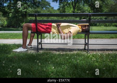 Vue latérale du jeune homme allongé sur banc de parc avec fedora covering face Banque D'Images