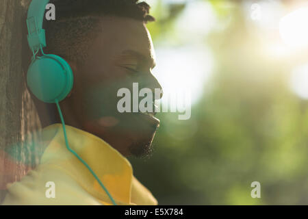Close up of young man with eyes closed listening to headphones in park Banque D'Images
