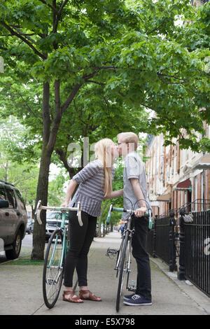 Jeune couple avec des bicyclettes, baiser sur street Banque D'Images