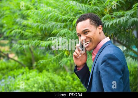 Businessman chatting on smartphone city park Banque D'Images