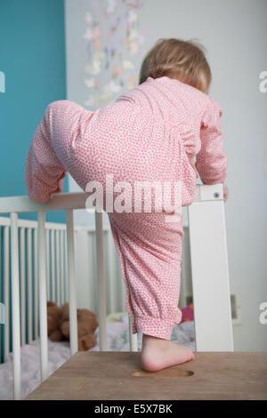 Vue arrière du female toddler montée au côté de lit-bébé