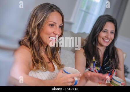 Deux amies bavarder autour d'un café dans la salle de séjour Banque D'Images