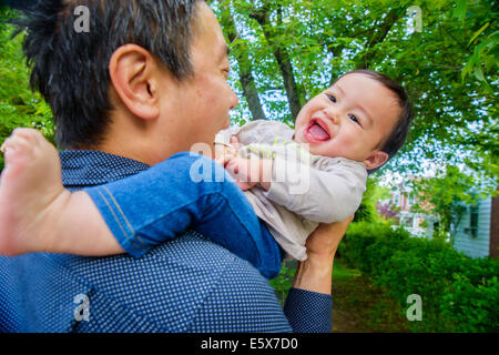 Mid adult father Playing with baby son in garden Banque D'Images