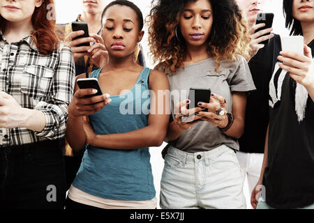 Portrait de six jeunes adultes texting on smartphone Banque D'Images