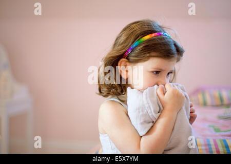 Malheureux fillette de trois ans dans la chambre maintenant pour faire face à une couverture confort Banque D'Images