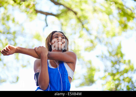 Young female runner stretching arms in park Banque D'Images