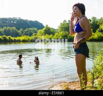 Jeune femme qui fume cigarette sur la berge du canal, Canal Delaware State Park, New Hope, Pennsylvanie, USA Banque D'Images