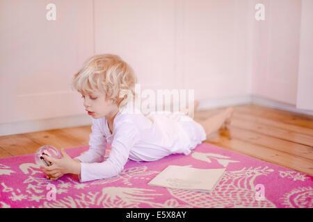 Quatre ans garçon couché sur un tapis à regarder snow globe Banque D'Images