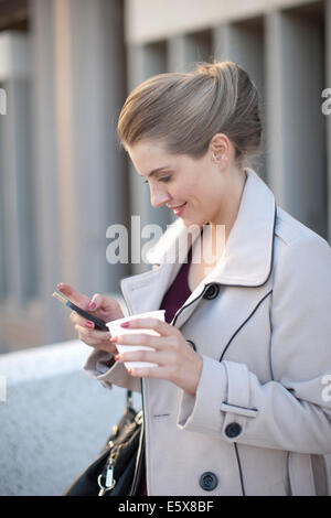 Young businesswoman texting on smartphone in city Banque D'Images