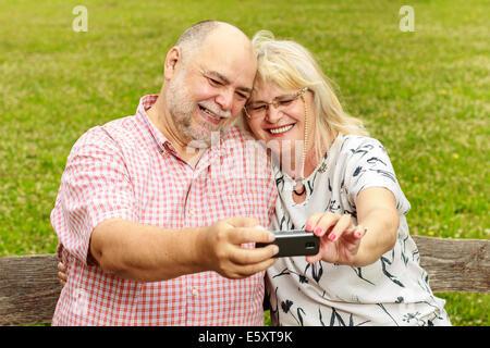 Happy senior couple prenant en selfies le parc. Banque D'Images