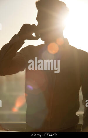 Man talking on cell phone, silhouetté par sun shining through window Banque D'Images