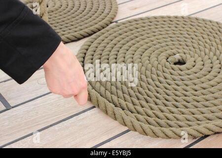 Nautique ancienne corde épaisse enveloppée dans de spirale de résisté, cercle de corde épaisse avec main de femme Banque D'Images