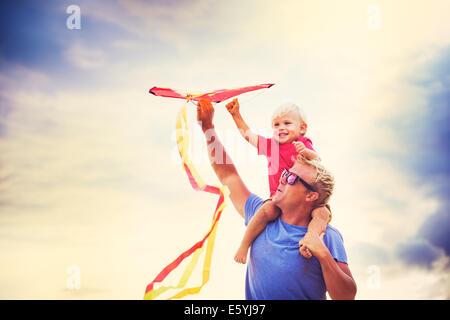 Sur l'épaule de son père au coucher du soleil le pilotage d'un kite ensemble Banque D'Images