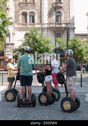 Les jeunes touristes sur Segway (véhicule électrique à deux roues) avec leur guide devant l'Opera House, Budapest, Banque D'Images