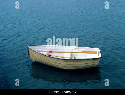 Un petit canot repose dans l'eau peu profonde et attend son propriétaire pour revenir et d'utiliser les avirons Banque D'Images