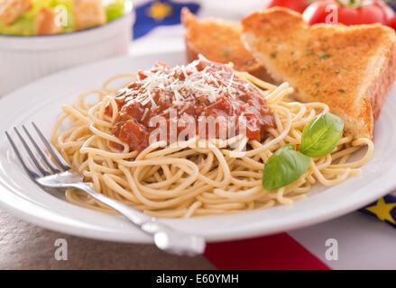 Des spaghetti avec sauce à la viande, pain à l'ail, et salade César. Banque D'Images