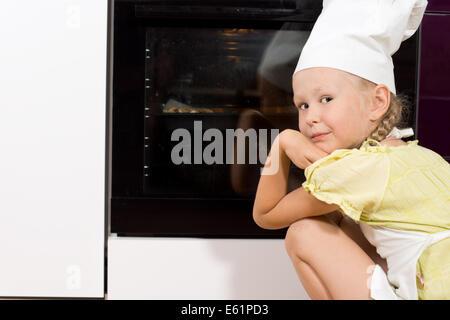 Petite fille portant un tablier blanc chefs hat et accroupi la regarder des pizzas cuire au four tournant à sourire Banque D'Images
