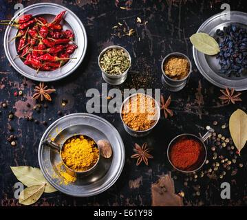 Ensemble d'épices poivre, curcuma, anis, coriandre en metal vintage tasses plus vieille table en bois. Vue d'en Banque D'Images