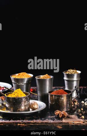 Ensemble d'épices poivre, curcuma, anis, coriandre en metal vintage tasses plus vieille table en bois Banque D'Images