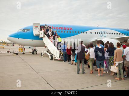 Les passagers de monter dans un avion de Thomson à l'aéroport de Gatwick, Londres. Banque D'Images