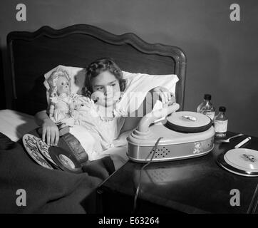 1950 fille malade au lit jouant RECORDS HOLDING BABY DOLL Banque D'Images