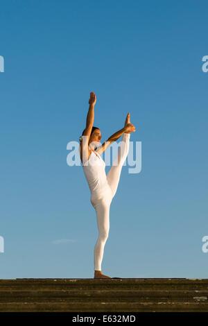 Jeune femme la pratique de l'Hatha Yoga, à l'extérieur, montrant la pose Anjaneyasana, soulevé la main pour poser Banque D'Images