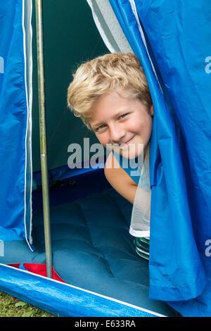 Un garçon, 10 ans, à sortir de sa tente. Banque D'Images