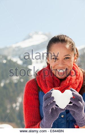 Portrait of smiling woman holding heart-shape snowball Banque D'Images