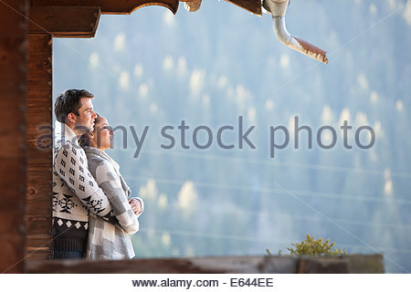 Couple hugging and looking at view de cabin porch Banque D'Images
