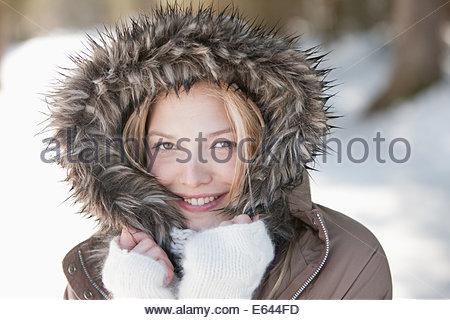Portrait of smiling woman wearing fur hood coat Banque D'Images