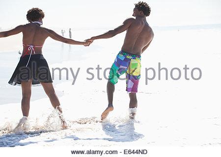 Couple en train de marcher dans les vagues sur la plage Banque D'Images