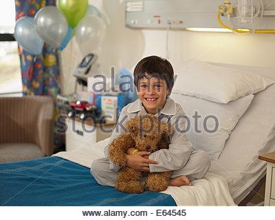 Garçon assis dans un lit d'hôpital avec ours Banque D'Images
