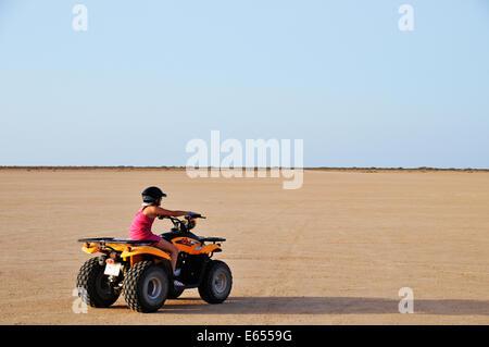 Jeune fille accélérant sur ATV quad dans le désert, la Tunisie, l'Afrique du Nord Banque D'Images