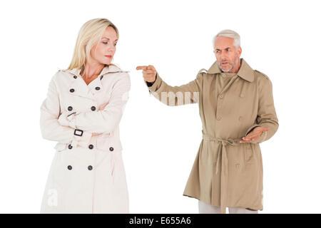 Angry couple combats en manteaux tranchée Banque D'Images