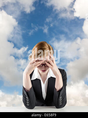 Image composite de redhead businesswoman with head in hands Banque D'Images