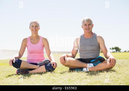 Mettre en place d'âge mûr assis en lotus poser sur l'herbe Banque D'Images
