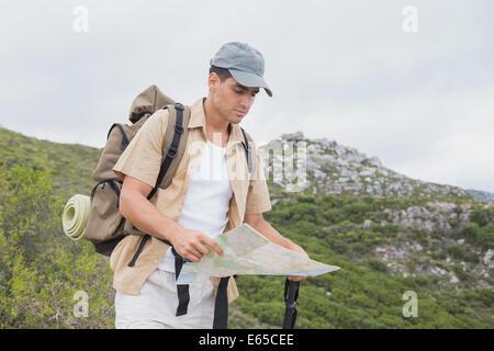 Randonnées homme tenant une carte sur un terrain de montagne