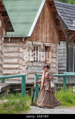 Femme en robe période log cabins and buildings le long de la rue principale de la vieille ville historique de Barkerville Banque D'Images
