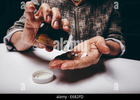 Portrait de femme âgée en prenant des médicaments sur ordonnance à partir de la bouteille de pilules. Les mains Banque D'Images