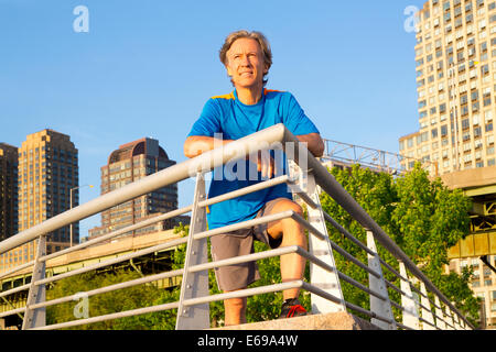 Young man leaning on railing in urban park