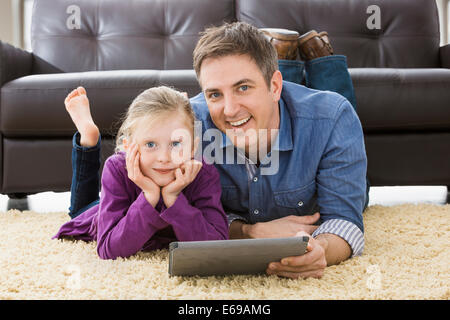 Caucasian father and daughter using tablet computer in living room Banque D'Images