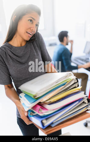 Hispanic businesswoman carrying stack of folders in office Banque D'Images