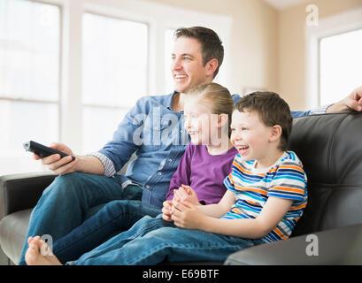 Père de race blanche et les enfants à regarder la télévision sur le canapé