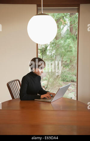Caucasian woman using laptop on table