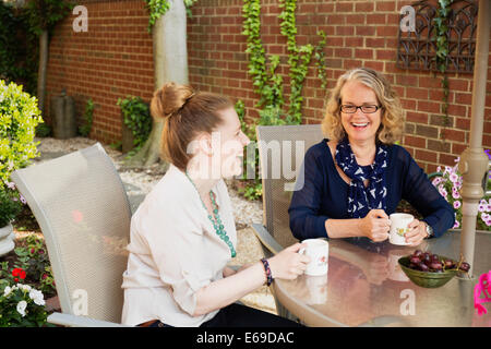 Caucasian mother and daughter drinking coffee in backyard Banque D'Images