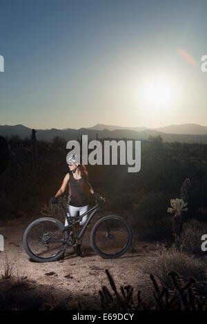 Mountain biker standing in desert Banque D'Images